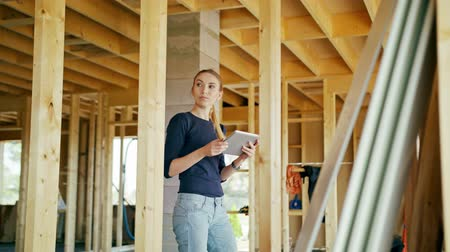 construtor : A young lady using a tablet in a house under construction. Long shot. Soft focus. Medium shot