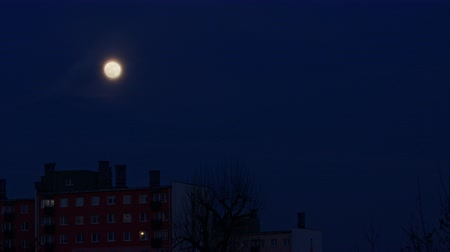 mensal : Full moon in the night sky over the city. Long shot