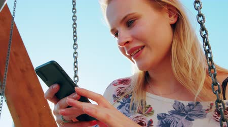 düşünürken : A young lady using a phone outdoors.