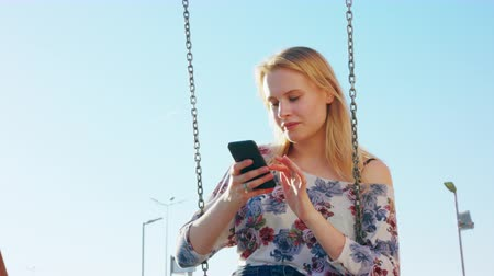 conectado : A young lady using a phone outdoors.
