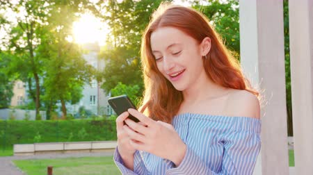phone call screen : A young lady using a phone outdoors.