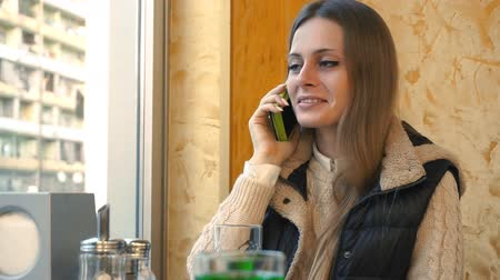 диалог : Smartphone woman having casual conversation on mobile phone laughing in cafe. Medium shot, handheld, slow motion 60 fps. Стоковые видеозаписи