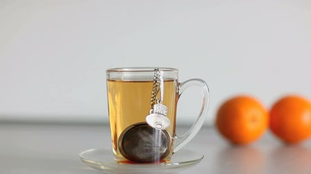 teabag : cup of strong black tea biscuit and two orange Stock Footage