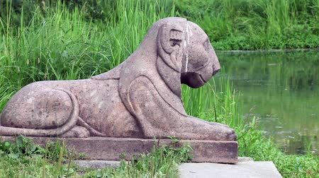 pinturas : stone lion sculpture on the shore of pond zoom in