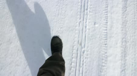 ślady stóp : Legs  feet making shadow of the person walks on a snow-covered road overhead shot close up