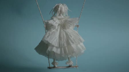 superstition : gloomy white voodoo paper puppet on swing Stock Footage