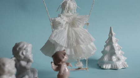 stopmotion : Little winged angel cherub learns to fly, animation stop motion, bible puppetry, doll on a swing, crisp white dress, Christmas, small children dream