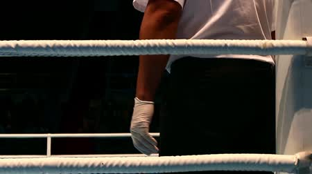 審判 : Boxing referee, corner ring ropes, strict black suit, rubber gloves, rear view camera goes down, floor ring spots of blood, time-out start boxing bout, bloody sport.