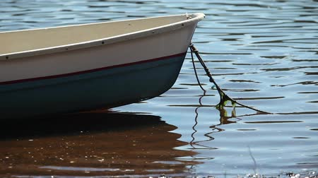 rowboat : Rowing boat moored at shore Swaying on the wave,  summer sunny day