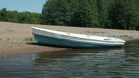 rowboat : Rowingboat moored at shore Swaying on the wave,  summer sunny day Stock Footage