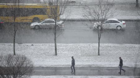 pehely : Winter Snowfall, cars a slowly driving along  road, single pedestrians in puddles in a hurry to get home Stock mozgókép
