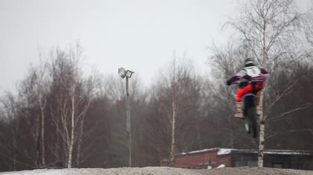 опасность : flight jumps  on motorcycle motocross back view.