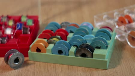 thread bobbins for sewing machine in box camera motion close up. Stock mozgókép