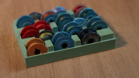 caixa de ferramentas : thread bobbins for sewing machine in box camera motion close up