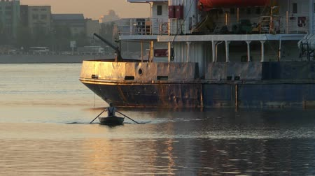 kürek çekme : Rowing boat goes on oars next to a large ship Stok Video