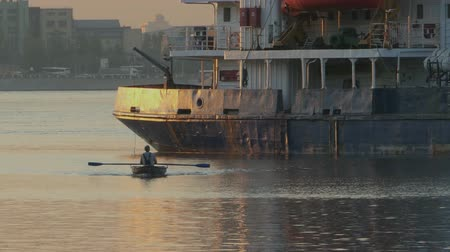 Rowing boat goes on oars next to a large ship Time lapse