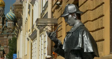 art : St. Petersburg, Russia, 24 May 2018 Sherlock Holmes smokes a pipe live sculpture on the street.