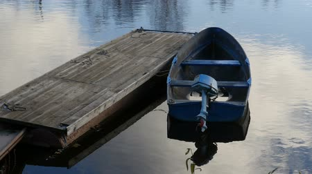 rowboat : Old boat with an outboard motor moored at the pontoon