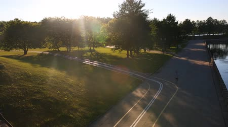 cape wheel : A cozy evening in the park. Bike Lane. People at sunset jog and ride a bicycle. View from above.