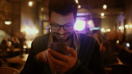 hipster : Young man sitting in night cafebistro browsing internet social media tablet and smiling mi
