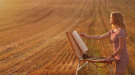 şövale : Young girl draws an image in the field at sunset. Creativity and inspiration.