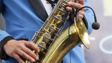 jazzman : Musician playing saxophone close-up. Wireless microphone saxophone. Man fingers pressing keys of the musical instrument. Saxophonist in blue suit playing on golden saxophone. Swing, jazz, blues music. Stock Footage