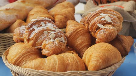 kruvasan : Sweet croissants in a basket on the table. Breakfast background with almond croissants. Delicious fresh croissants, close-up