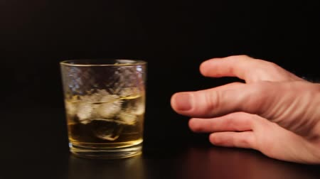 slayt : Glass of alcohol sliding across the bar counter, slow motion. Hand picks up a drink.