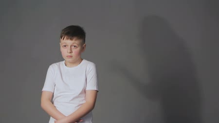 scold : Shadow of angry mother scolds frightened son. Domestic violence and children abuse concept.