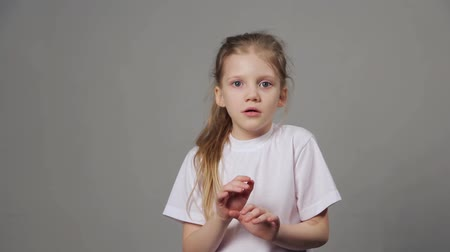 chocado : Scared young girl expressing fear emotion isolated on grey background. Concept of emotions. Stock Footage