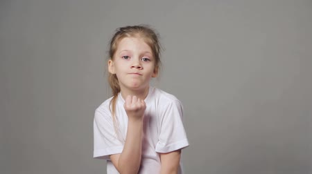 ameaças : Portrait of young angry girl threatens with a shaking fist isolated on grey background. Concept of emotions. Stock Footage