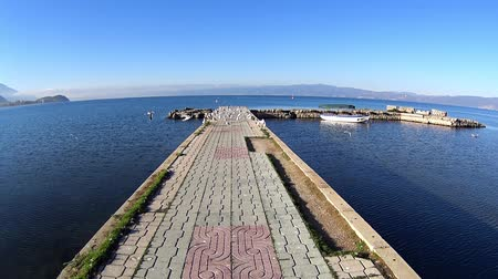 ohrid : POV birds flying from jetty by Lake Ohrid on sunny day, Macedonia Stock Footage