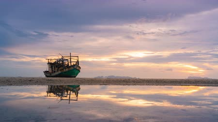 elpusztított : Old wrecking fishing boat beached and reflection on puddle in sunset time at Samui island, Suratthani, Thailand