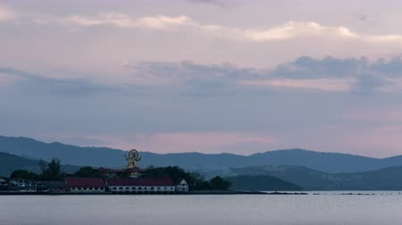 Clouds move over Wat Phra Yai or big buddha temple in Samui island, Thailand while sunset twilight time and located near the beach