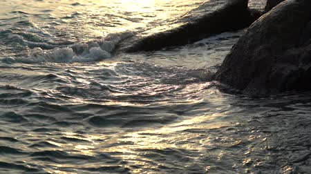 Close up golden sea wave hitting the rock in sunrise