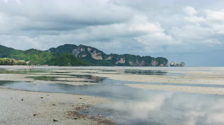 aonang : Clouds move over the beach and reflect on puddle in low tide sea in Nopparat thara at Krabi, thailand