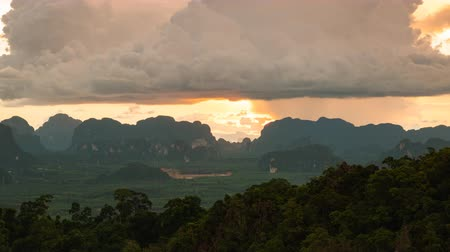 província : Sundown through heavy clouds and shine the light between mountains valley and make bloody sky in tiger cave temple at Krabi province, Thailand