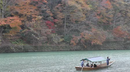 KYOTO, JAPAN - DECEMBER 1: Boatman punting the boat for tourists to enjoy the autumn view along the bank of Hozu river on December 1, 2012 in Kyoto, Japan.