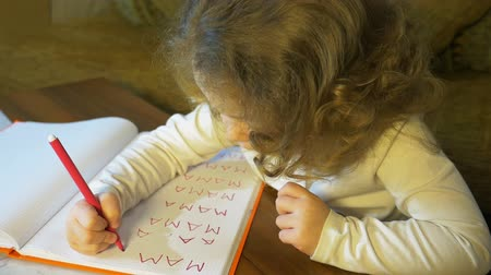small pen : Little girl learns to write the word mama