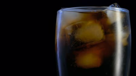 tonik : Spinning glass of fresh cola with ice cubes and bubbles in close up
