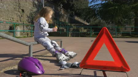 łokieć : The child is resting and eat snacks in the park on rollerblade