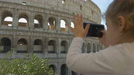 kleine meisjes : Cute little girl taking pictures of the Colosseum on a smartphone