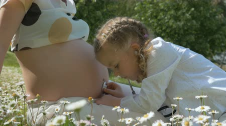 возможность : Cute little girl with stethoscope play doctor with pregnant mother. A girl with pigtails examines mothers belly. Happy Mother and Daughter having fun outdoors and enjoying nature together.