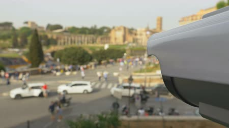 zsaru : Remotely controlled surveillance camera monitors security in the city. CCTV camera aimed at a crowd of people and cars on the road near the Colosseum. First-person view footage