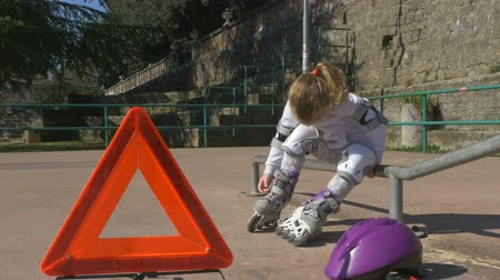 skate : Trouble with rollerblading on a playground, emergency warning triangle a front of sad little girl, conceptual footage