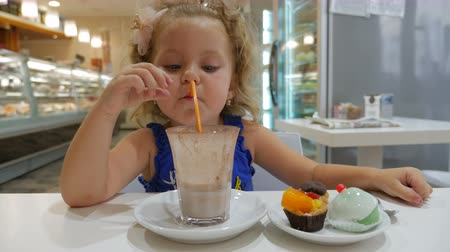 çikolata : Beautiful little girl enjoying a delicious chocolate drink with cupcakes Stok Video