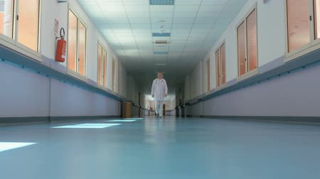 rywalizacja : Disappearing jobs and modern technology. The doctor walks down the hospital corridor and slowly disappears, robots replacing jobs, conceptual footage
