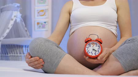 mensal : Pregnant woman with a clock in hand symbolizes quickly passing nine months of pregnancy. Pregnancy month by month. An expectant mother in final month of pregnancy