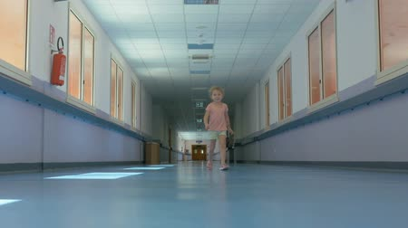 pré escolar : The little girl is walking along the bright empty corridor. Long clean corridor of modern educational institution.