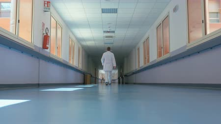 replace : Robots replacing jobs. Doctor in a white uniform with a stethoscope is going along the corridor of a large modern hospital and slowly disappears. Conceptual footage